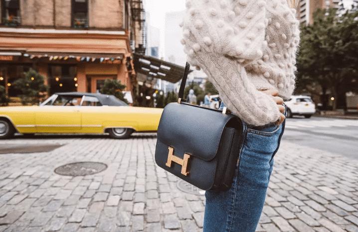 Woman Holding a Black Hermes Handbag